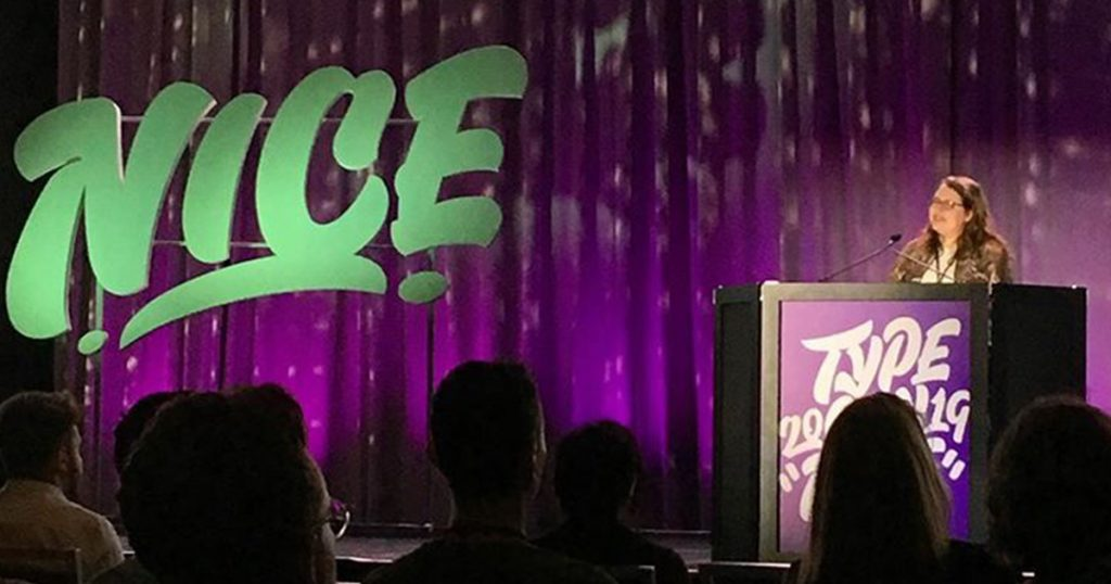"""A purple backdrop on a stage, a small person standing behind a podium and the word """"NICE"""" in teal on the stage next to her"""