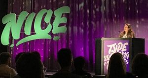 "A purple backdrop on a stage, a small person standing behind a podium and the word ""NICE"" in teal on the stage next to her"